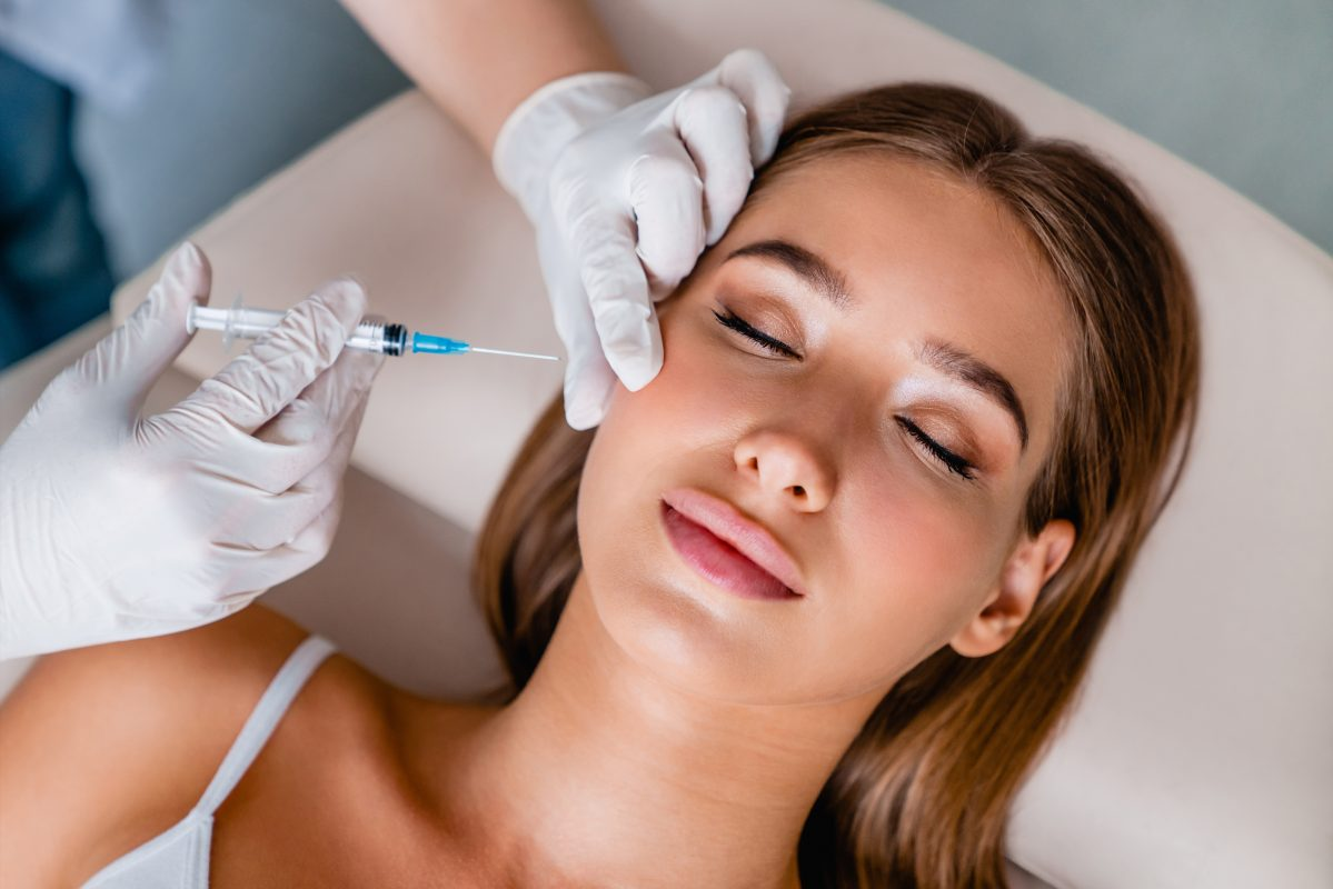 Young woman getting injection in cheek